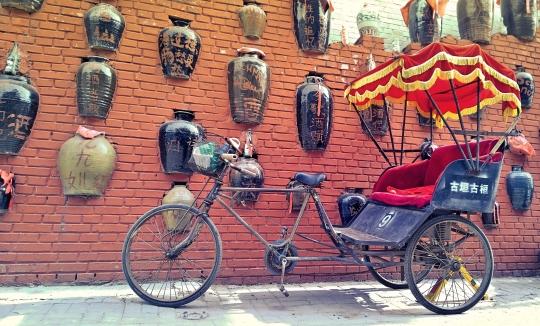 Fahrrad-Rikscha vor einer mit antiken Schnapskrügen verzierten Hauswand; Beijing Gulou